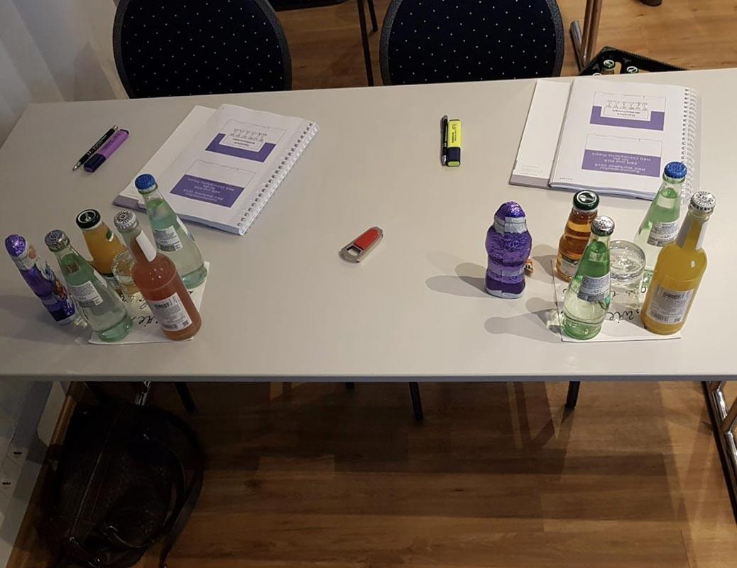 Seminarunterlagen liegen zwischen Getränken bei Fortbildung für zahnärztliche Abrechnung